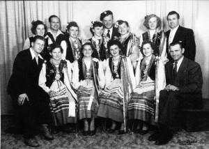 Photographie en noir et blanc de quatorze personnes, dont neuf femmes en habit traditionnel ukrainien et cinq hommes en habit chic.