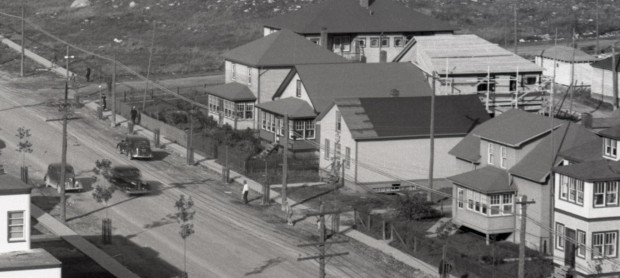 Black-and-white photograph of five adjacent buildings made of wooden planks. There are several cars travelling and people walking on the sidewalks.