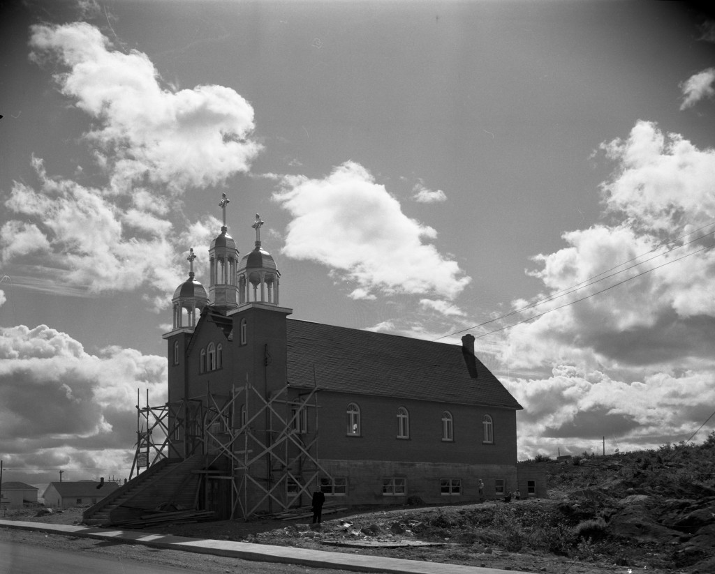 Black-and-white photograph of a church with three steeples, three crosses and a front enclosed within a scaffold. In the foreground, you can see steps leading to the main doors.