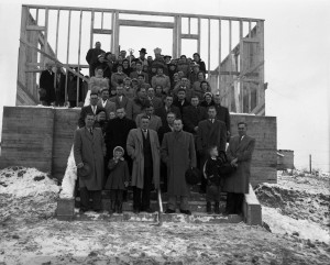 Black-and-white photograph of about 70 people on stairs in front of a wood structure. There are two Catholic priests, a Roman priest and a Ukrainian priest.