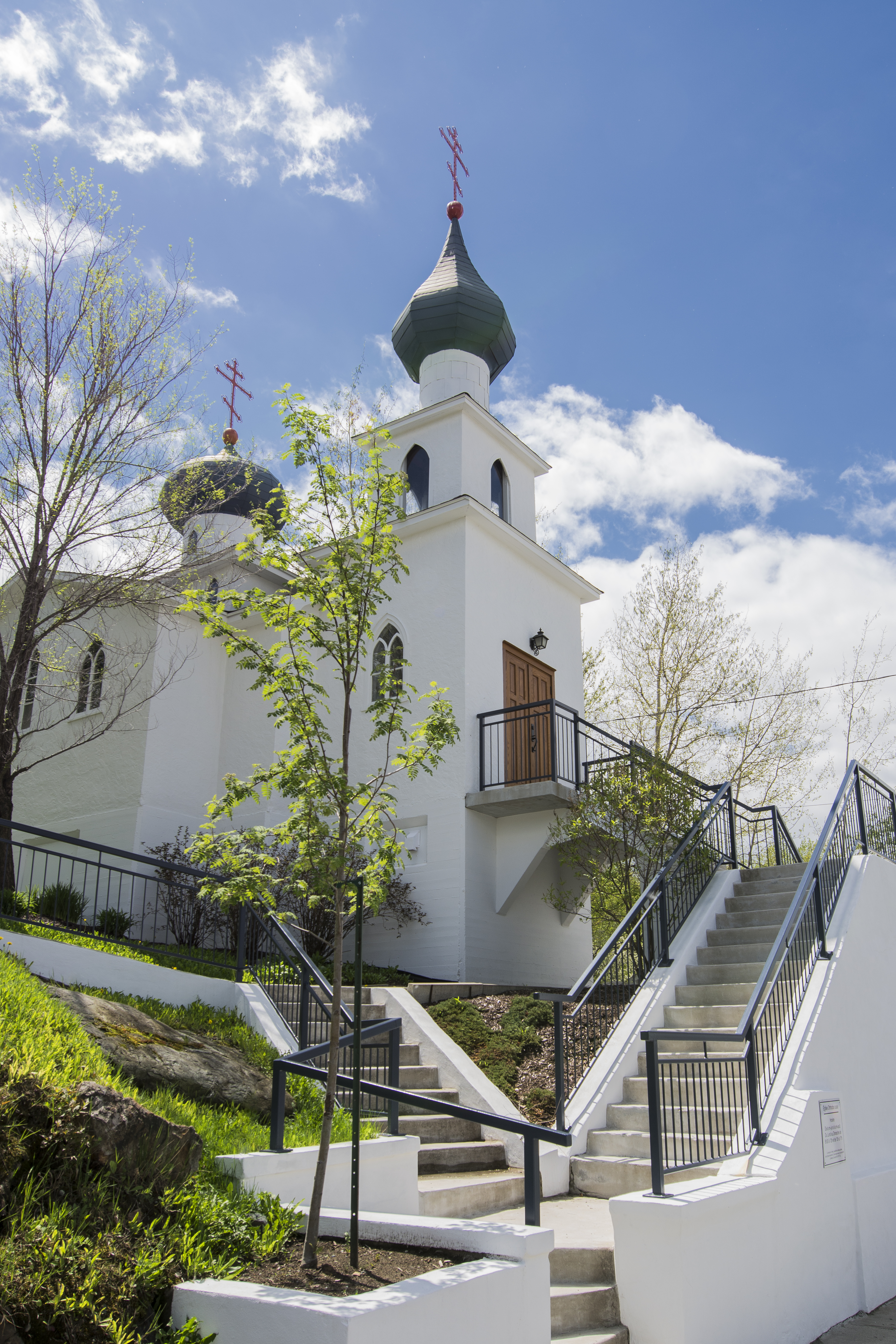 Colour photograph of a white church with orthodox crosses overlooking two bulb-shaped steeples. Concrete stairs lead to the main door and to the back of the church.