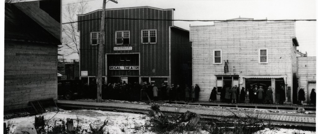 Black-and-white photograph of two buildings with boomtown-styled fronts. On one of them, there is a sign where it is written Regal Theatre. A crowd waits on the boardwalk in front of the building.