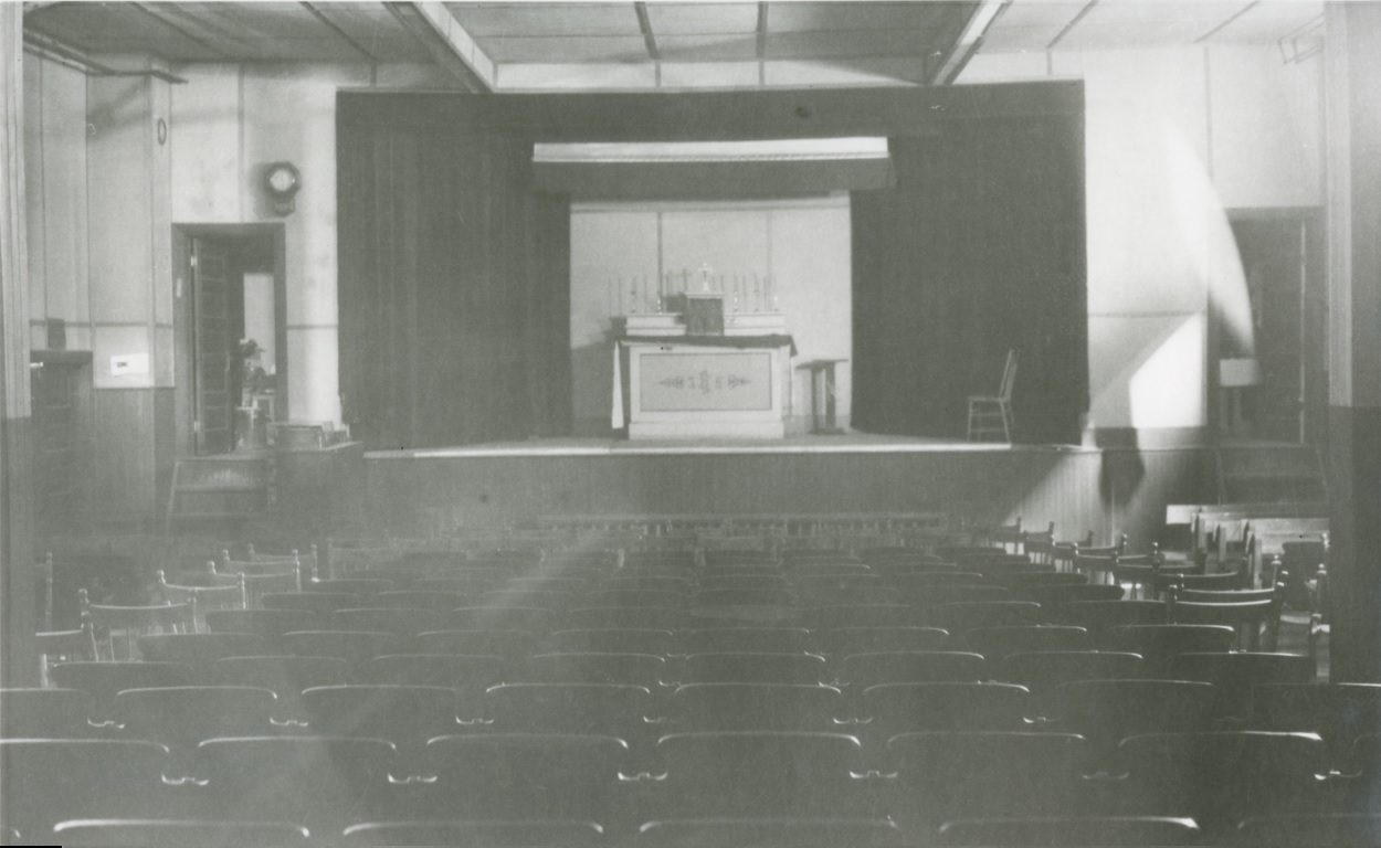 Black-and-white photograph of a theatre with both fixed and moveable chairs. On the stage there is an altar on which lies a tabernacle.