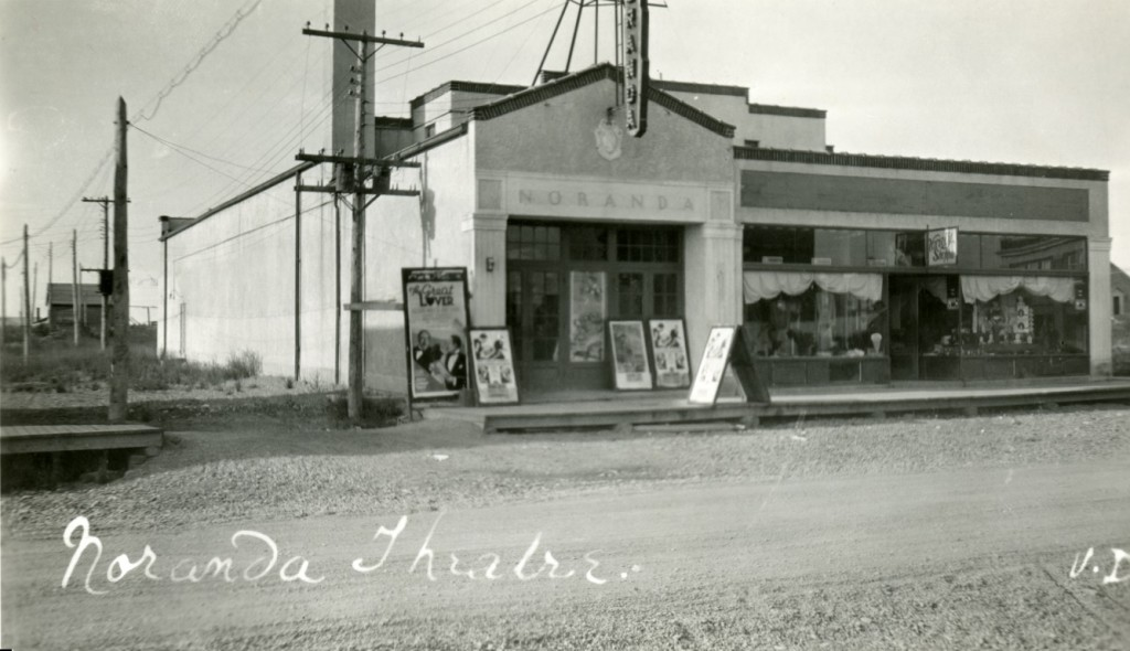 Black-and-white photograph of a building with Noranda written on the front. Several movie posters are hung on the boardwalk.