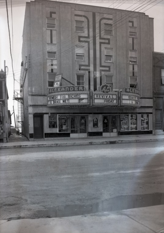 Black-and-white photograph of a four-story building with a theatre on the ground floor. You can see which movies were playing by reading the titles displayed at the entrance.