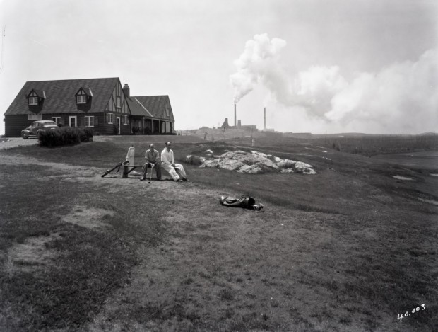 Black-and-white photograph of two men sitting in a lodge of the Golf Club of Noranda with the Horne mine in the background.