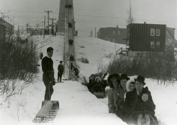 Black-and-white photograph of several people sliding on a wood structure installed on a hill.