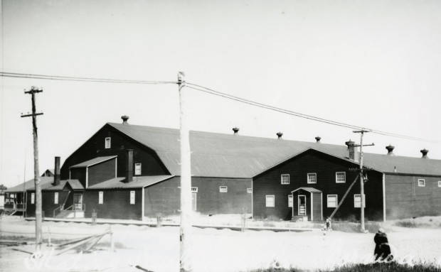 Black-and-white photograph of two buildings with tin roofs and very few windows. A blanket of snow covers the ground.