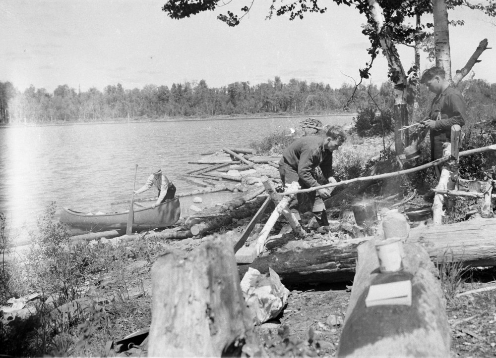 Black-and-white photograph of three prospectors. One of them is paddling a canoe while the two others are lighting a fire.