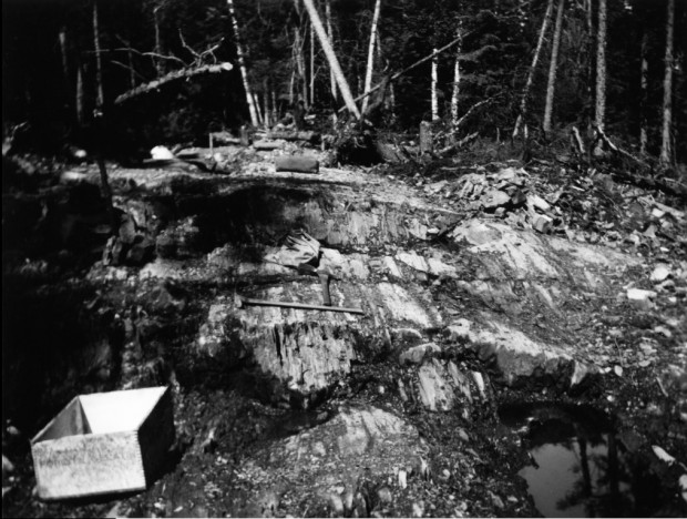 Black-and-white photograph of rock soils with two pickaxes and two wood box. There is a forest in the background.