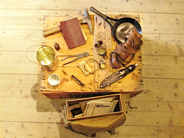 Colour photograph of about 15 prospecting artifacts spread out on a wood box and a canvas bag laying on the ground with a wood structure inside it.