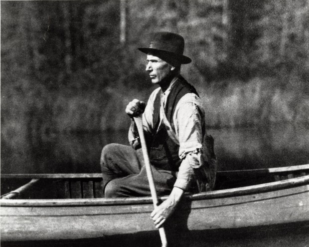 Black-and-white photograph of prospector Edmund Horne paddling on a lake with the forest in the background.