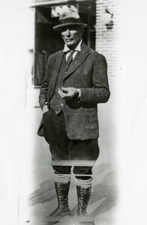 Black-and-white photograph of prospector Edmund Horne wearing a suit, high-cut boots and holding a cigar.
