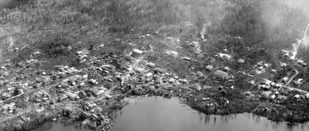 Black-and-white photograph of approximately 100 log cabins built in a chaotic way on the shores of Osisko Lake.