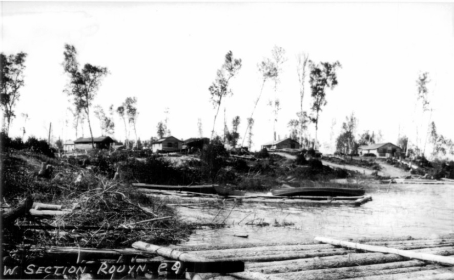 Black-and-white photograph of several log cabins on a small tree-lined hill. On the foreground there is a lake with a rudimentary dock as well as a few canoes.