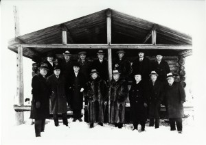 Black-and-white photograph of 15 men in fancy suits, three of whom are wearing fur coats, standing in front of a log cabin.