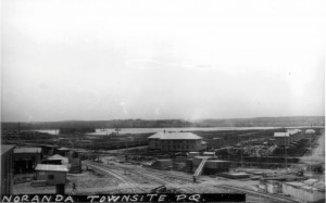 Black-and-white photograph of the construction site of the soon-to-be city of Noranda. You can see Osisko Lake in the background, the railroad in the foreground and the mine executives' house on the right.