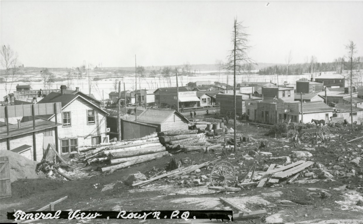 Black-and-white photograph of rudimentary buildings southwest of Osisko Lake. In the background, you can see rocks, timbers, wooden planks and waste.