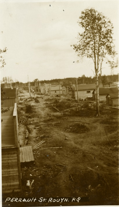Black-and-white photograph of two rows of rudimentary buildings with boardwalks and trees in the middle.