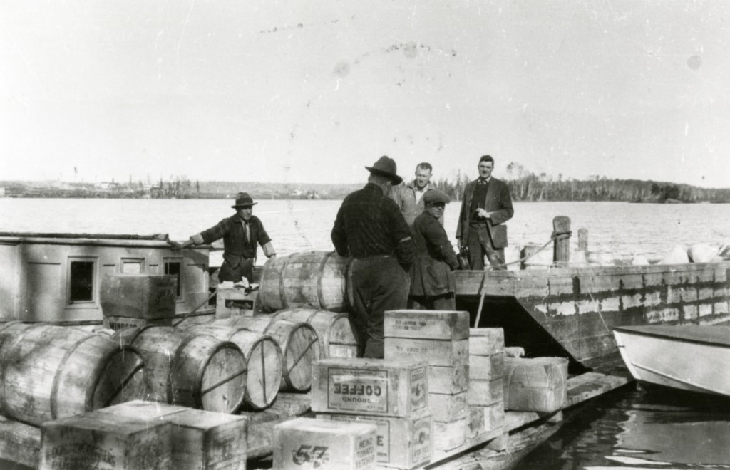 Black-and-white photograph of five men on a dock in the process of unloading crates and wood barrels.