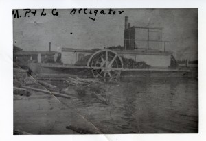 Poor quality black-and-white photograph of a docked steamboat. On the shores, a building and logs are floating on the water.