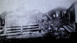 Poor quality black-and-white photograph of several rudimentary buildings. On the foreground you can see a log cabin.