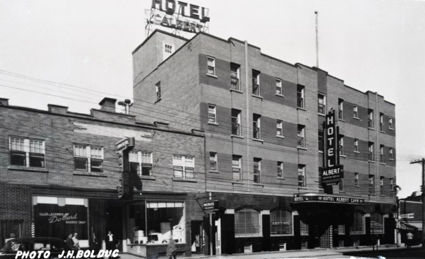 Black-and-white photograph of a four-story building with several signs, including one on the roof that reads, Hotel Albert. On the left, you can see a two-story building.