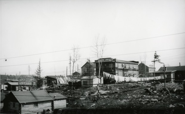 Black-and-white photograph of several rudimentary buildings made of planks or timbers. On one of the boomtown-styled fronts, you can read Hôtel Bellevue on a sign.