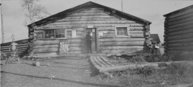 Black-and-white photograph of a timber building, in front of which there is a boardwalk to the entrance. In the front, we can see a man in a suit and a gas pump.
