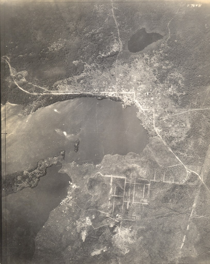 Black-and-white photograph, taken from a plane, of Rouyn and Noranda in their early days. A lake is in the middle of the photo. It is hard to see details from this height, but you can still see that the city of Rouyn is more populated than its neighbour Noranda.