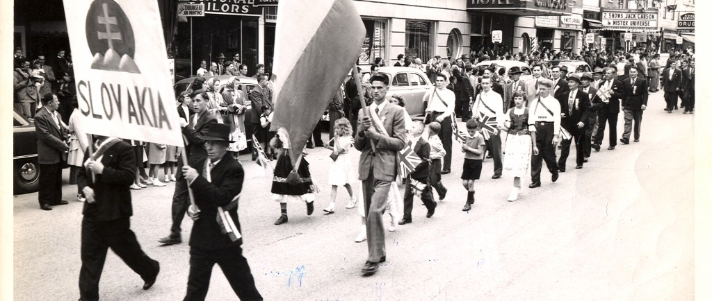 Black-and-white photograph of 25 people who parade before a crowd looking at them from the sidewalks. They're marching in a parade with a sign that reads Slovakia decorated with the national coat of arms and a Slovakian flag.