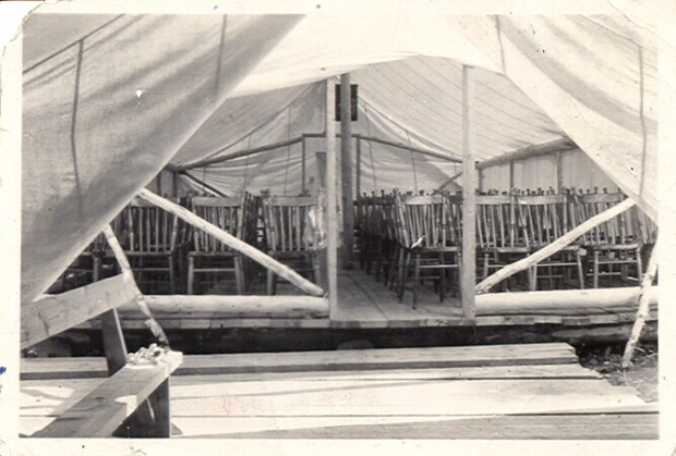 Black-and-white photograph of a tent interior showing rows of chairs and a hardwood floor.