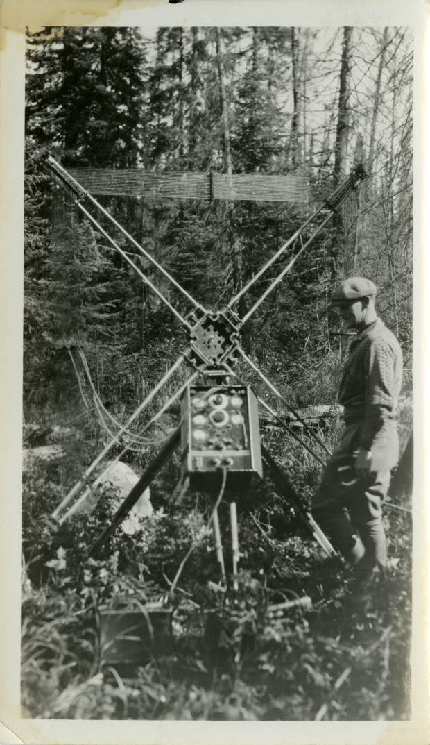Black-and-white photograph of a man in work clothes standing beside the control panel of a device with four crossed antennas. A forest is visible in the background.