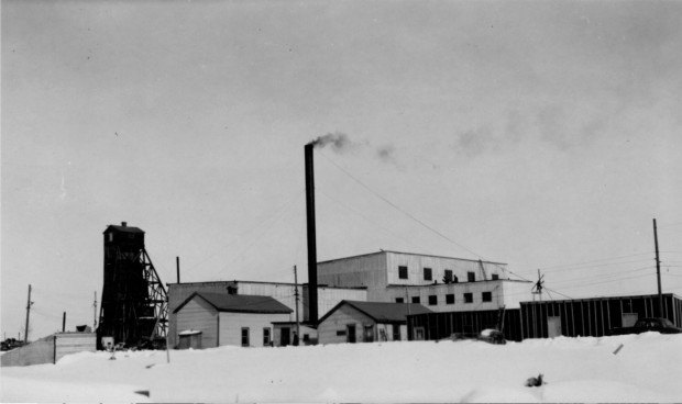 Black-and-white photograph of several mining buildings made of planks, including a headframe and a chimney and featuring a blanket of snow on the ground.