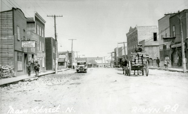 Black-and-white photograph of a gravel road where a car and a carriage are driving. People are walking on the boardwalks. The buildings have boomtown-styled fronts. A sign reads, Chong Lee Laundry Buanderie.
