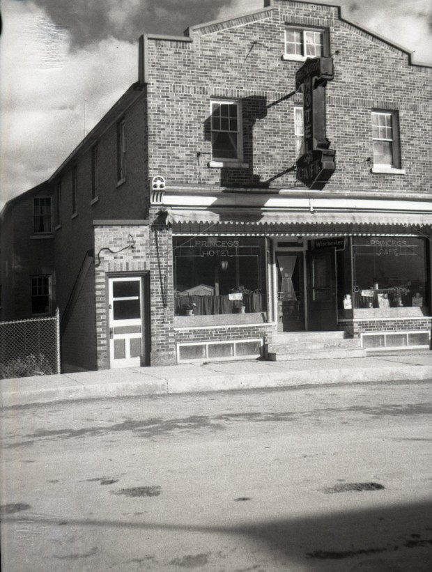 Black-and-white photograph of a three-story brick building. On the middle of its front, you can read Princess Hotel and on the left, you can see a door apparently leading to a basement.