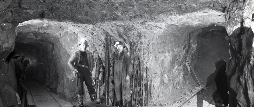 Black-and-white photograph of the intersection of three roads inside a mine. There are two railroad tracks on the ground and two men pose in front a drill machine and a steel structure.