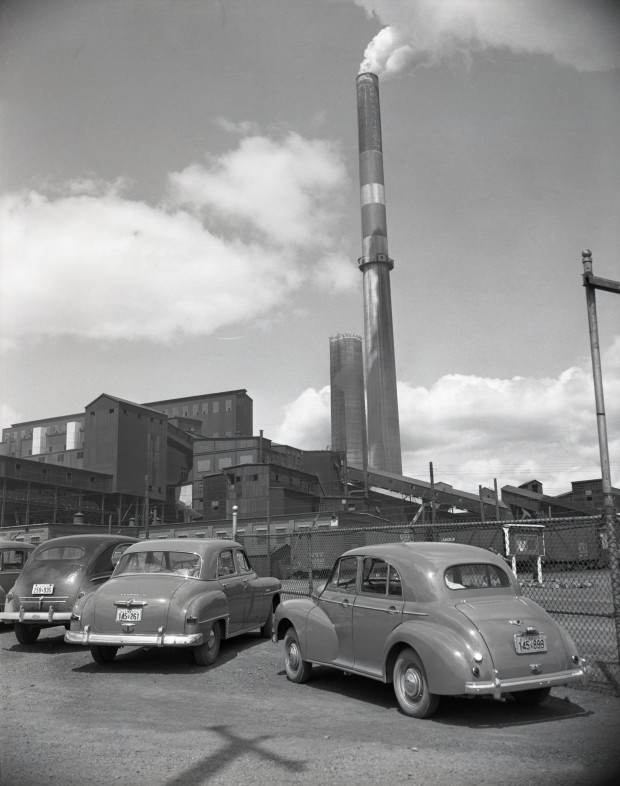 Black-and-white photograph of three old cars parked in front of the Horne mine's fence. You can see the smelter with smoke rising from a chimney in the background.