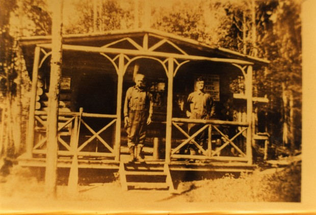 A sepia-toned photograph of two men standing on the porch of a log cabin with a forest in the background.