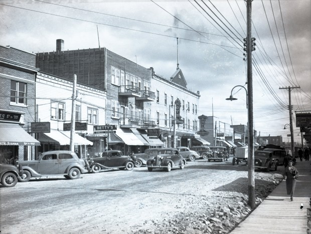Black-and-white photograph of a street lined with two or three-story buildings on which there are signs for some of the stores' name. You can see several people walking on the boardwalks as well as cars that are either parked or rolling.