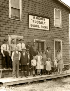 Black-and-white photograph of several women and children before a building whose sign reads, A. Niemen Ruckala Board & Rooms.