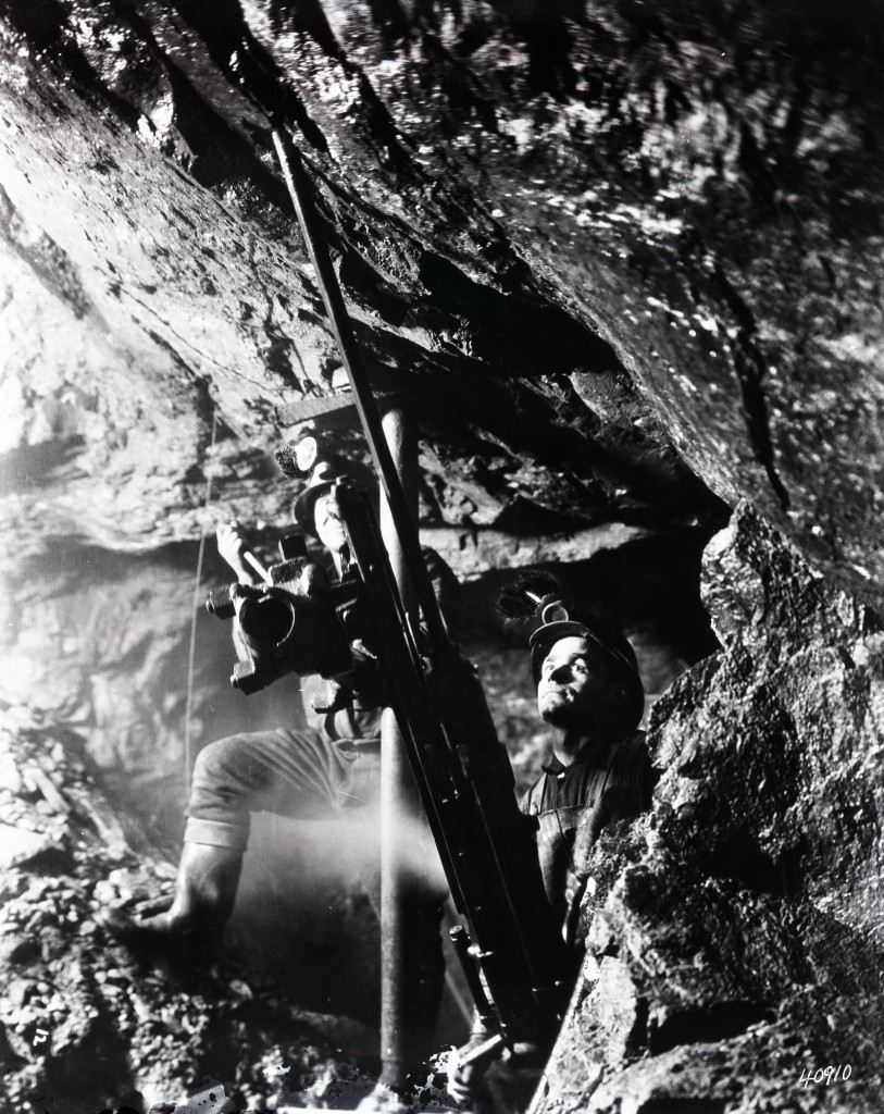 Black-and-white photograph of two miners operating a drill mounted to the ground and roof with metal rods. The men wear rubber boots and a helmet with a light.