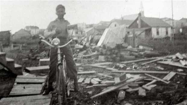 Black-and-white photograph of a little boy on a bicycle, posing in front of a pile of planks and logs. In the background, you can see houses and a church.