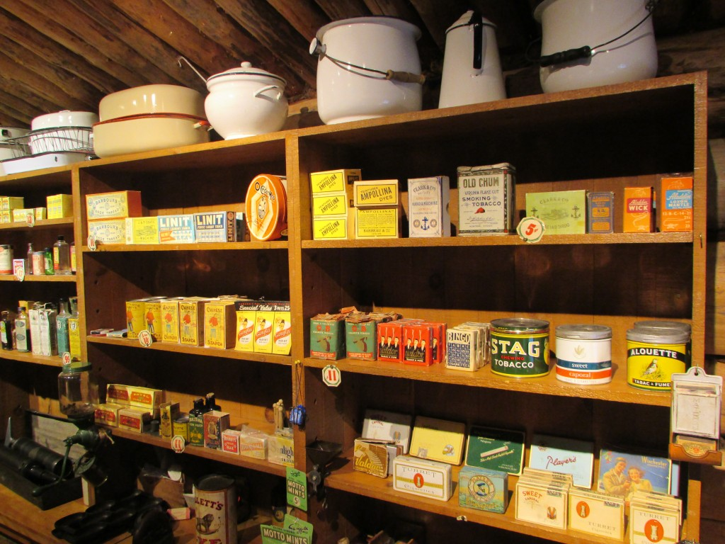 Colour photograph of three shelves filled with products from the 1920s.