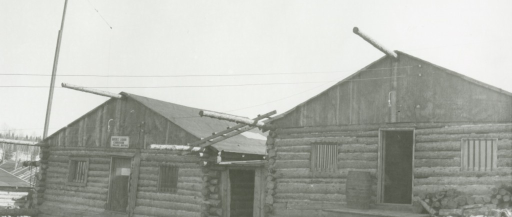 Black-and-white photograph of two log cabins with bars on the windows. A sign is put up on the door of the left building.