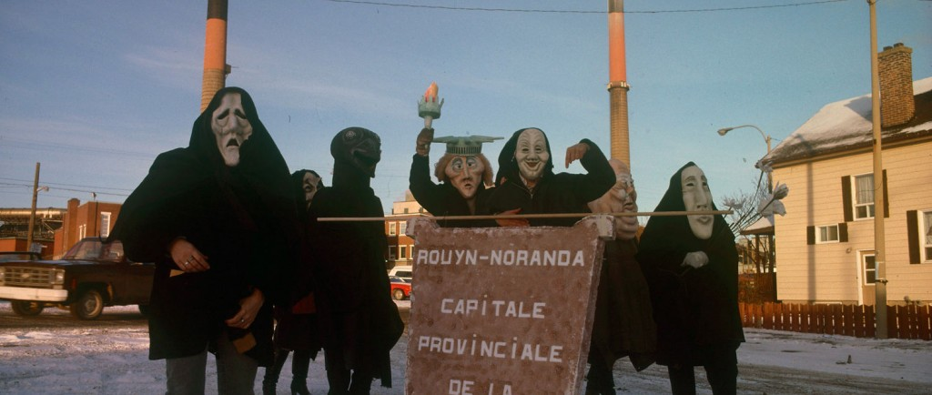 Colour photograph of seven people in front of the Horne smelter. They are costumed and carry a poster that reads in French Rouyn-Noranda provincial capital of pollution.