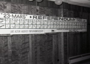 Black-and-white photograph of a board labelled 23 mars Référendum, 1986. The results from each polling stations are written. There is a wooden lath wall and balloons floating on the ceiling.