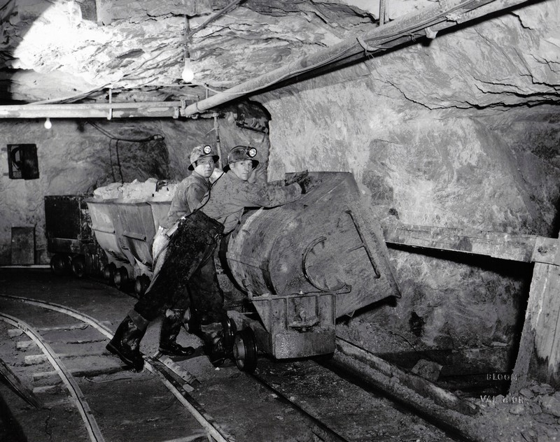 Two miners unloading a cart of crushed rock in the ore pass.