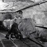Deux mineurs qui déversent un chariot dans une chute à minerai