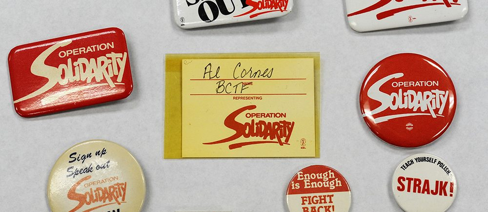 A collection of Operation Solidarity buttons, a delegate badge, and a pin from the Polish Solidarnosc union.